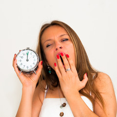Yawn-beautiful young woman holding alarm clock