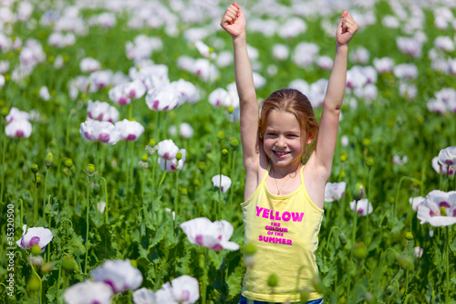 Young girl with hands up in field of white poppy