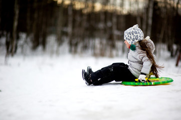 Adorable child girl sledding in snow on a saucer