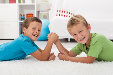 Happy boys laughing and arm wrestling