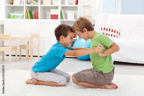 Two happy boys wrestling