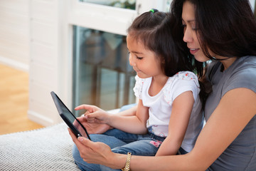 Mother and daughter reading electronic book