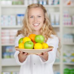 lächelnde apothekerin zeigt obstkorb
