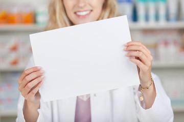 apothekerin zeigt weißes plakat