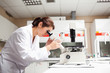Female scientist looking in a microscope