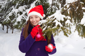 woman in Santa hat decorates  fir-tree