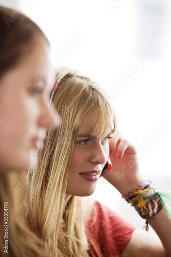 Two teenage girls on a bus, one girl talking on a mobile phone