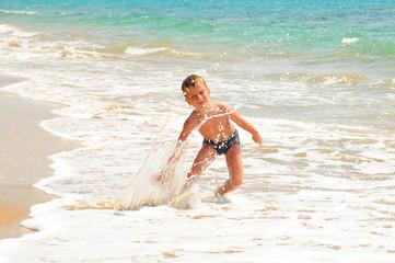 Junge spielt am Meeresufer