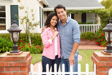 Hispanic couple outside new home