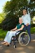Pflegerin schiebt Rollstuhl