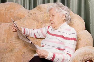 The elderly woman reads newspaper