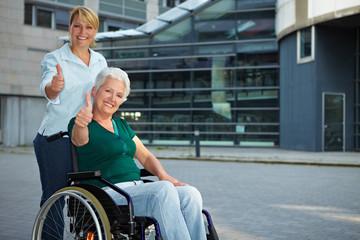Rollstuhlfahrerin zeigt mit Daumen nach oben