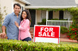 Hispanic couple outside home with for sale sign