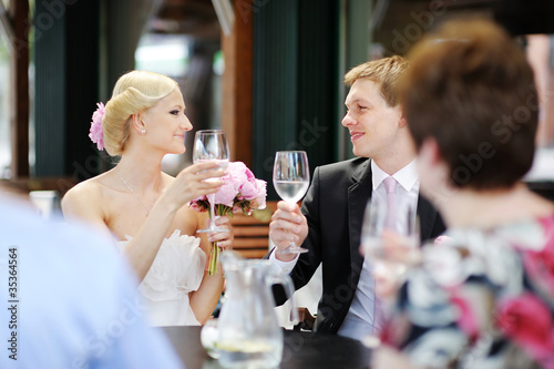 Bride and groom drinking champagne at their wedding