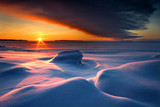 Snowy seascape with dark cloud and rising sun
