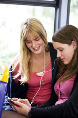Two teenage girls sitting on a bus, listening to music