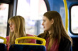 Two teenage girls sitting on a bus, looking out of the window