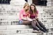 Two teenage girls sitting on steps, writing postcards