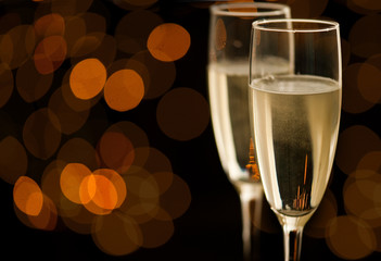 Two glasses of champagne with golden bokeh