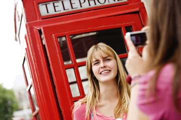 Two teenagers taking photographs in front of a telephone box