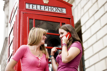 Two teenage girls laughing, one girl talking on her mobile phone