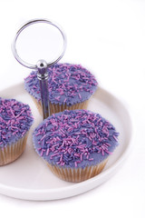 Vanilla cupcakes, decorated with lavender-coloured buttercream a