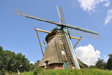 Dutch grain windmill on a small hill