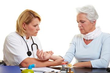 Ärztin fühlt Puls bei Blutdruckmessung