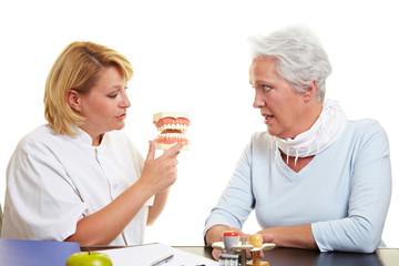 Zahnärztin erklärt Patientin Behandlung