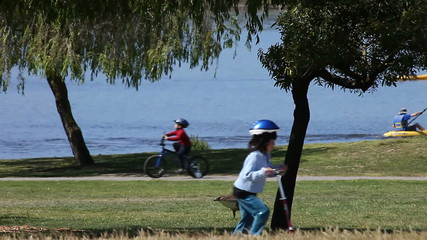boaters and bicyclists enjoy a sunny day at the park