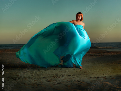 woman on beach wind blowing blue dress