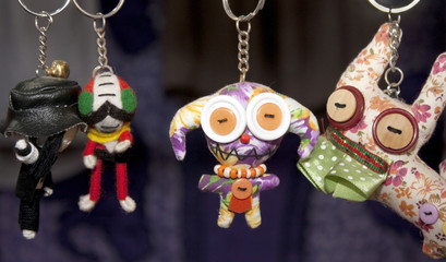 many dolls in key rings hanging in line