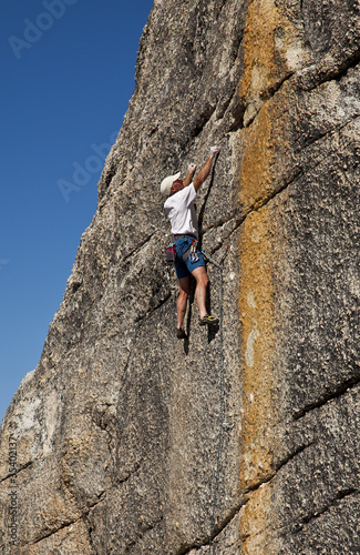 Male rock climber clings to a cliff.