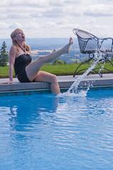 Laughing woman on swimming pool edge splashing