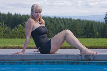 Attractive woman sits beside a swimming pool