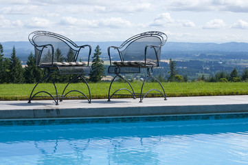 Wrought iron patio chairs beside a swimming pool