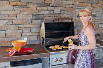 Attractive woman using a gas barbeque grill