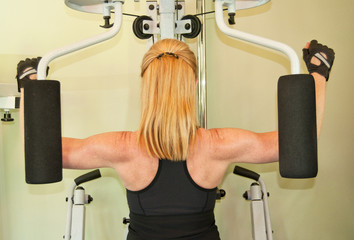 Fit blond woman uses exercise machine