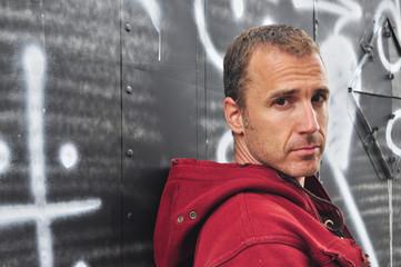 Serious Caucasian man against a graffiti wall
