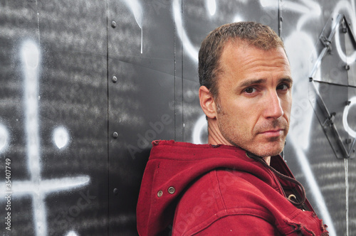 Serious Caucasian man against a graffiti wall