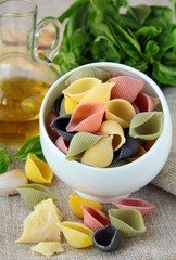 uncooked tricolor pasta in cup  with  olive oil