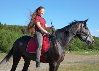 A girl with long hair on a horse