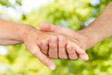 Closeup of old people hands holding together outdoor