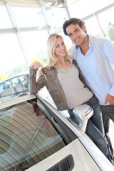 Happy couple holding new car keys