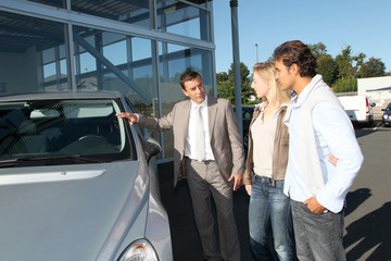 Car seller showing vehicle to couple of purchasers