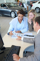 Car seller and couple looking at catalogue