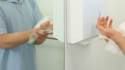 Man drying hands with paper towels in a bathroom