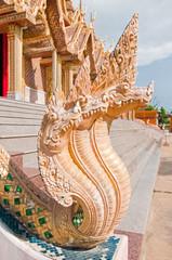 Naga statue infront of Thai style golden castle