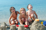 Three kids making sand castle by the sea - Fine Art prints