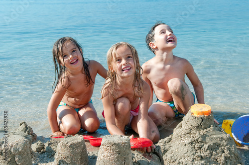 Three kids making sand castle by the sea